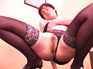aged dame with short hair in dark nylons gives a