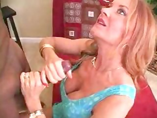 milf redhead performs a tugjob on a dark chaps