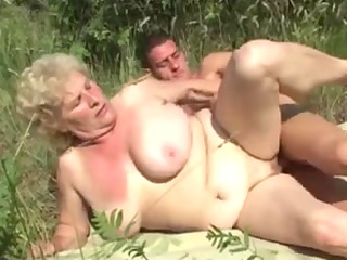 german granny outdoor with youthful dude by troc