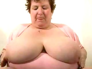 fat, breasty granny is showing off her large